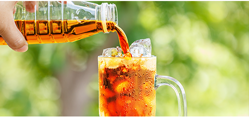pouring bottled iced tea outdoors